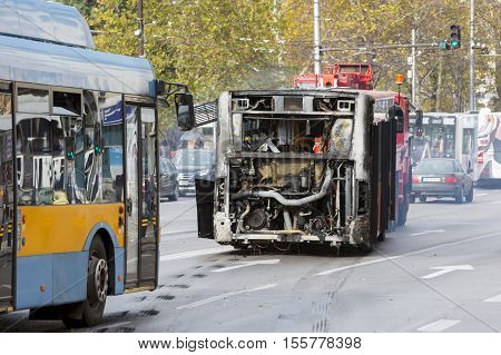 Sofia Bulgaria - November 8 2016: Burnt public traffic bus is seen on the street after caught in fire during travel and extinguished by firefighters.