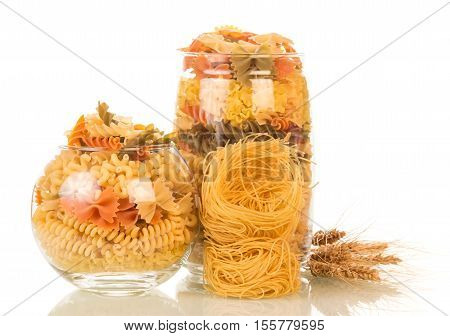 Jars with colored pasta isolated on white background.