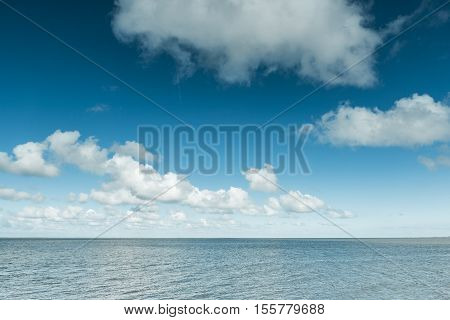 Nautical background of a calm blue ocean on the North Sea Coast Germany on a sunny day with fluffy white clouds in a blue sky in a panoramic view