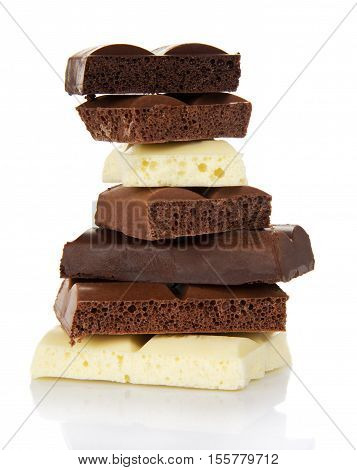 Stack of porous pieces of milk and black chocolate isolated on a white background.