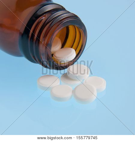 White pills poured out of bottle close up