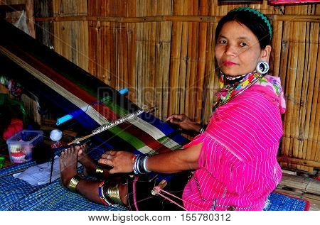 Chiang Mai Thailand - December 26 2012: Thai hilltribe woman sitting on a mat weaving fabric on a hand loom at the Baan Tang Luan Cultural Village