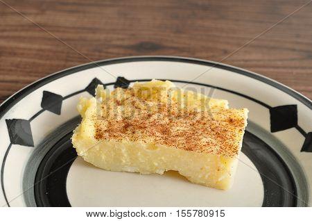 A slice of milk tart in a plate