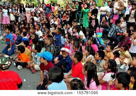 Chiang Mai Thailand - December 27 2012: A rapt audience of school children watching a performance during an outdoor assembly at their school on Chang Puak Road