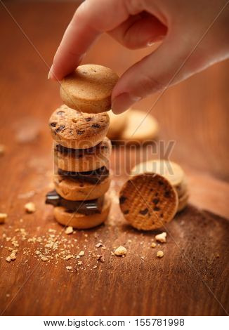 Female Hand Puts Small Bisqiut Cookies On Each Other With Chocolate Pieces Between And Makes Turret