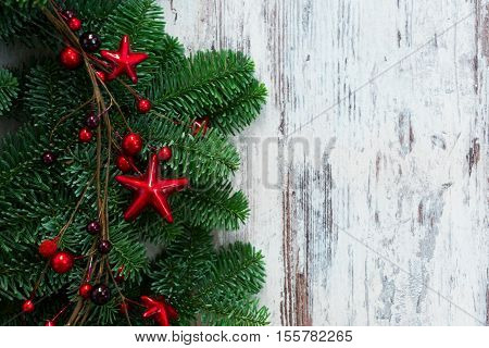 christmas fresh evergreen tree branches with red garland on aged wooden background