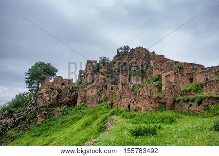 Abandoned village Gamsutl in Dagestan. Scenic landscape with ruins of lost city in mountains poster