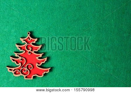 Red Christmas tree carved on the green background of the texture, wooden eco decoration, toy