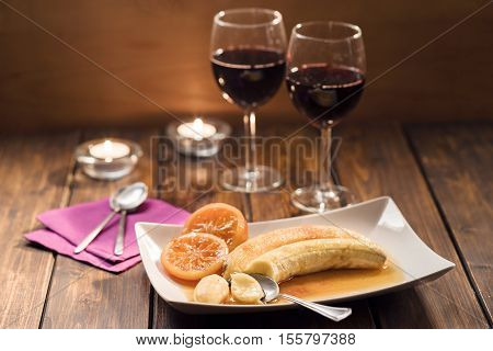 Bananes flambe with caramelized oranges with two glasses of wine in rustic style