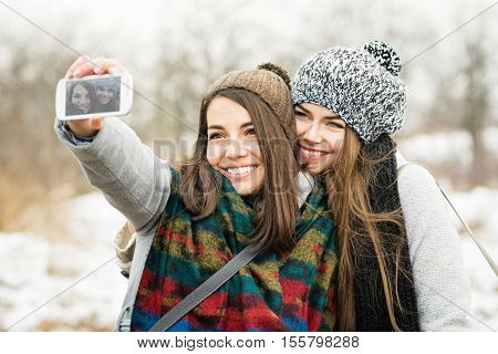 Two beautiful teenage girls taking a selfie in winter using smart phone. Closeup of happy young women photographing together wearing winter outfit and knitted hats. Natural light, mild retouch.