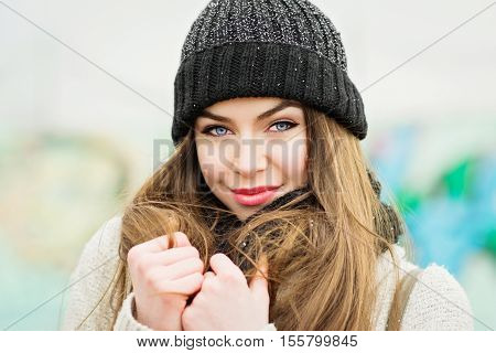 Closeup of gorgeous young blonde teenage woman in knitted beanie hat. Beautiful blue eyed female posing, smiling, outdoors in winter. Retouched, natural lighting.