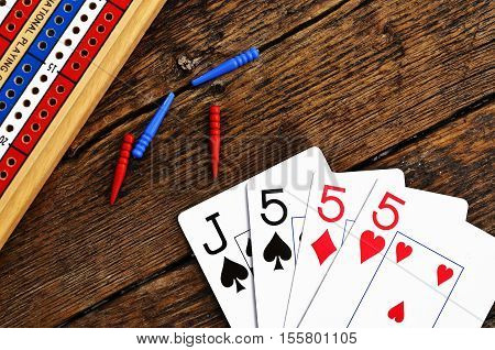 A top view image of a wooden cribbage board and cards.