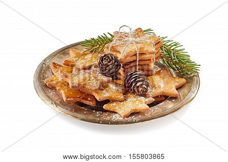 Composition of star shaped ginger cookies and pine cones on old metal dish. Isolated on white background. Christmas concept.