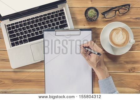 Young business man hands with pen writing blank paper on on desk table with cup of coffee glasses and laptop computer. Top view business concept.Vintage tone