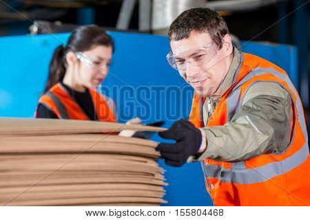 Workers with cardbord stacks near conveyor in distribution warehouse