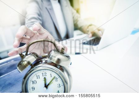 Business people write something about meeting subject on laptop computer hand holding the clockbusiness concept and film effect.