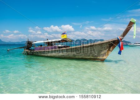 Long tail boat on crystal clear water at Chicken Island (Koh Kai), Krabi Thailand