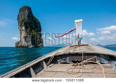 Prow of long tail boat with view of beautiful sea, blue sky and huge rock in Krabi, Thailand