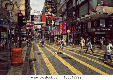 Hong Kong - October 2016: Mong Kok shopping street with colorful signboards and people on crosswalk. Retro look. Kowloon