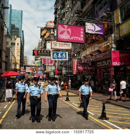 Hong Kong - October 2016:  Group of Police officers walking at Mong Kok shopping street with colorful signboards in background. Kowloon