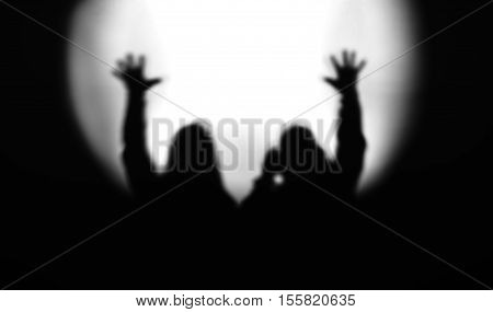 Black and white couple silhouettes with hands up in light of floodlight backdrop