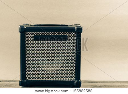 Guitar amplifier isolated on a light brown