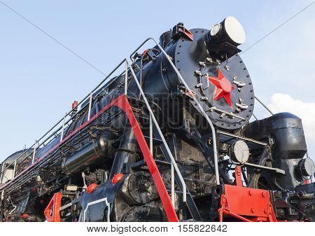 photographed close-up of an old steam locomotive black and red colors, against the blue sky