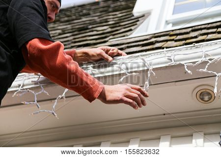 man adjusting the hanging strands of Christmas lights as he hangs them on the eavestrough