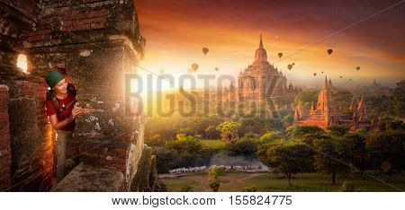tourist with a backpack explores the ancient temple on a background of beautiful sunrise with balloons. Bagan Myanmar. Traveling along Asia active lifestyle concept.