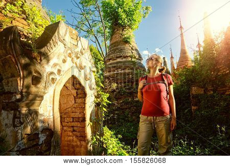 Traveler with a backpack looks at ancient Buddhist stupa of the temple complex In Dein Inle Lake. Mayanmar