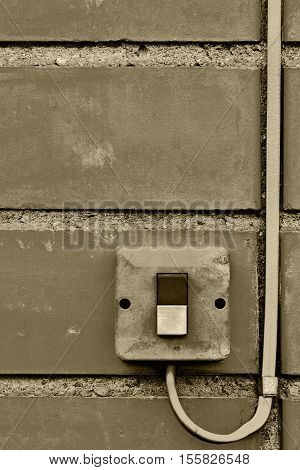 Outdoor electric equipment control industrial button switch wire cable closeup, old aged weathered grungy brick wall background texture pattern, large detailed vertical textured grunge copy space in sepia