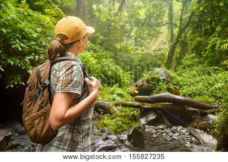 Young backpacker with backpack traveling along rain forest. Lombok Indonesia. Tourist hiking in the deep jungle