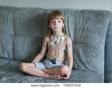 Child sitting on the sofa. Heart cardiogram or monitoring of cardiac performance using Holter.