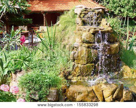 Beautiful Waterfall In  Garden In Summer.