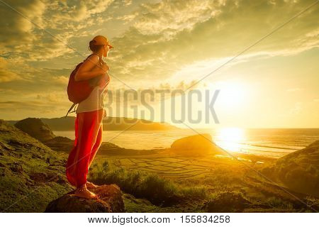 A young traveller looking at sunset on the island Lombok Indonesia. Traveling along Asia active lifestyle concept