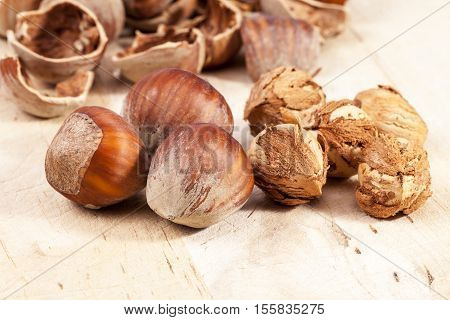 Composition of hazelnuts and husks on wooden plank close up