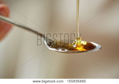 healthy food, eating and ethnoscience concept - close up of honey pouring to teaspoon