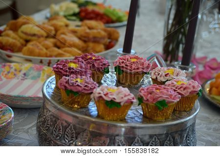 A table of party food. A beautiful tray of elaborate cupcakes that look like flowers.