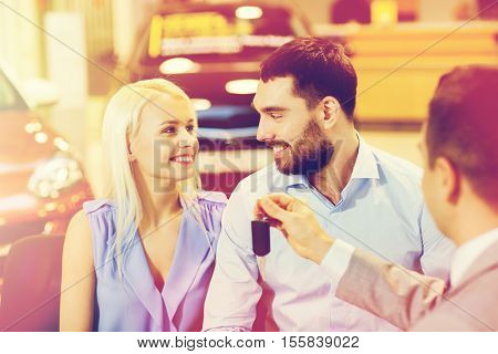 auto business, sale and people concept - happy couple with dealer giving car key in auto show or salon