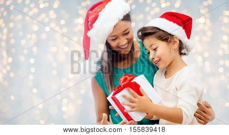 christmas, holidays, celebration, family and people concept - happy mother and child girl in santa helper hats with gift box over lights background