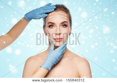 people, cosmetology, plastic surgery and beauty concept - surgeon or beautician hands touching woman face with lifting arrows over blue background and snow