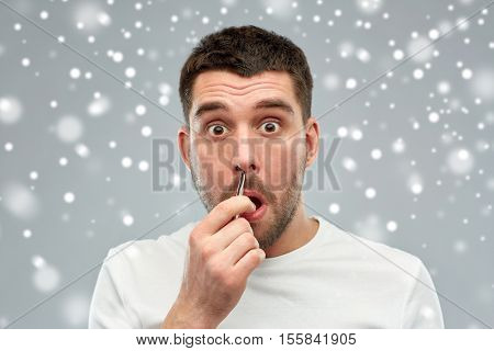 beauty, winter, christmas and people concept - smiling young man with tweezers tweezing hair frome nose over snow on gray background