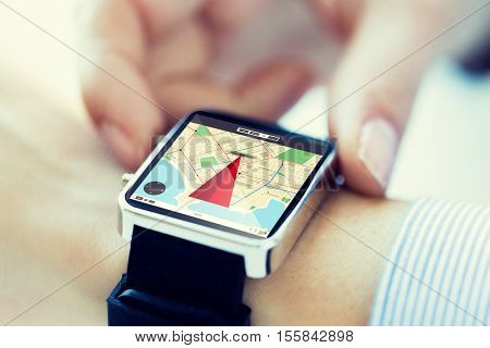 technology, communication, travel, navigation and people concept - close up of woman hands setting smart watch with navigator map on screen
