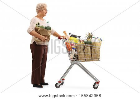Full length profile shot of an elderly woman with a bag and a shopping cart filled with groceries waiting in line isolated on white background
