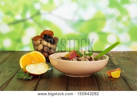 A bowl of oatmeal, fruit, glass with nuts and dried fruits on abstract green background.