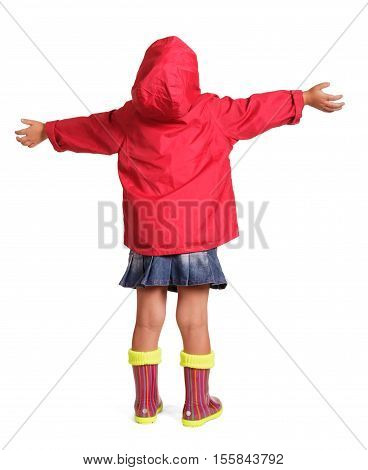Little girl in a red jacket, blue skirt and rubber boots standing with arms outstretched isolated on white background. Back view.