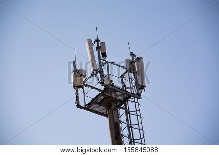 Top side of mast with an equipment for cellular communication. Tower with platform and stairway.