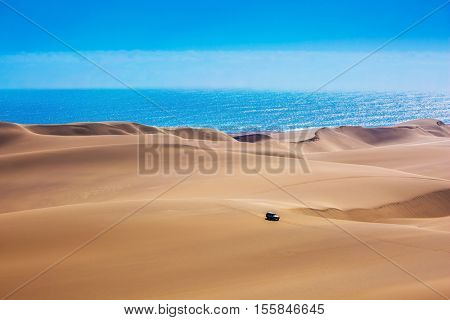 Huge sand dunes moving on the Atlantic coast. Sandwich Harbour - part of Namib-Naukluft National Park. Tourist trip by jeep