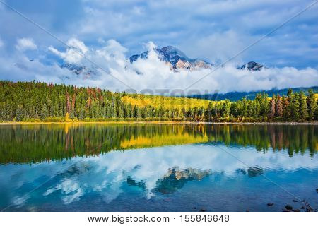 Charming Patricia Lake amongst the evergreen forests, yellow grass and distant mountains. Warm autumn in the Rocky Mountains of Canada