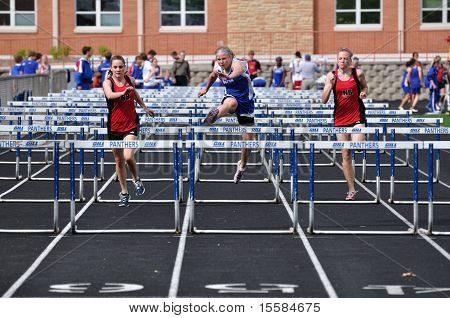 Teen Girls Competing In High School Hurdles Race